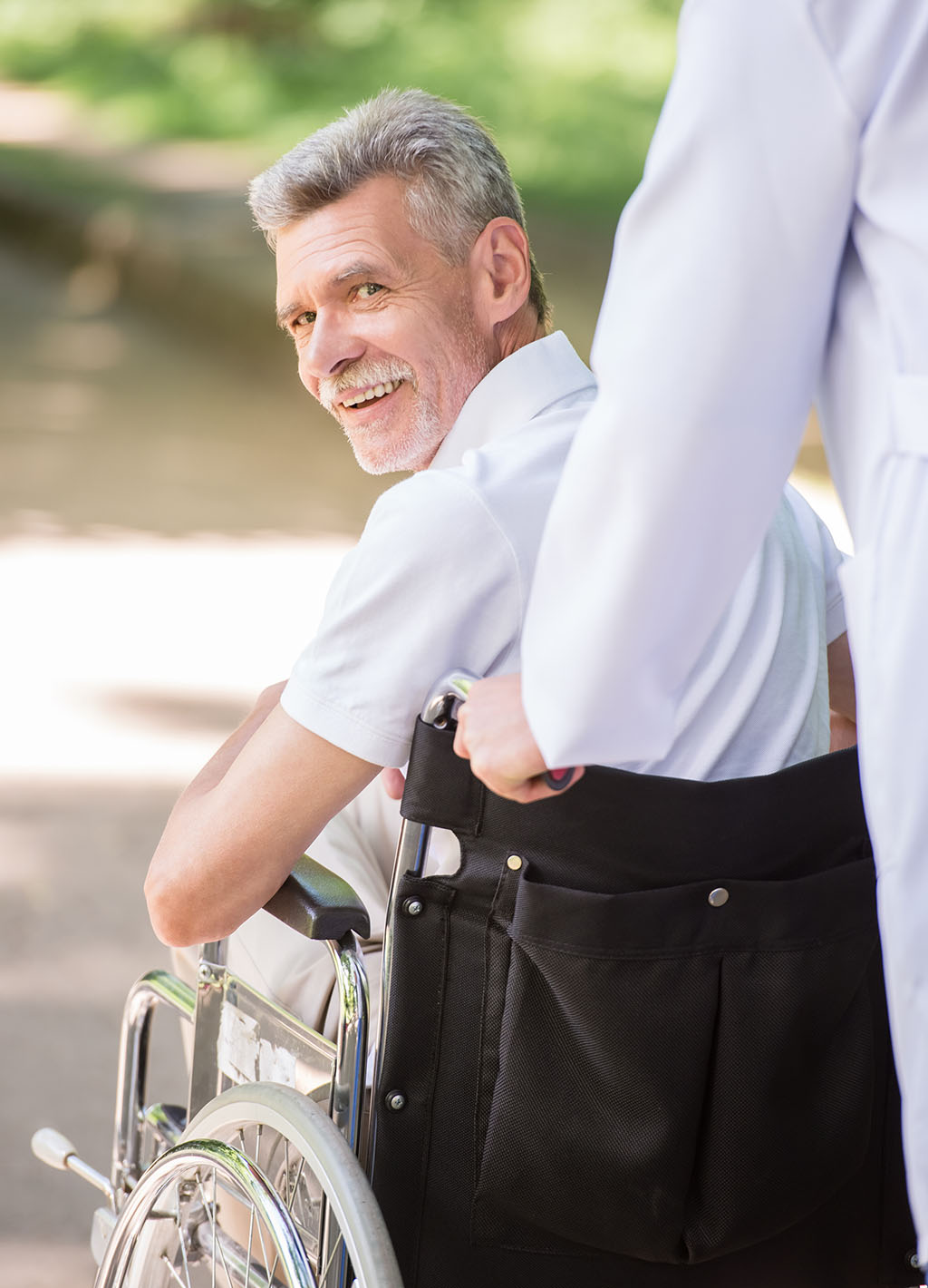 Male nurse pushing a senior patient in wheelchair outdoor on a sunny day.